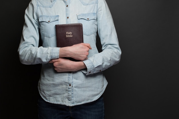 Mujer sosteniendo una biblia en manos vistiendo ropa casual sobre fondo gris