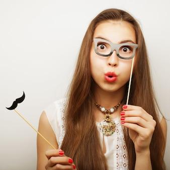 Mujer sosteniendo bigote y gafas en un palo