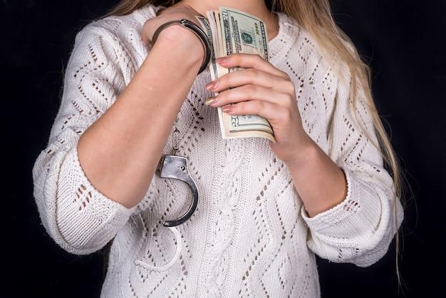 Mujer sosteniendo billetes de un dólar con las manos esposadas