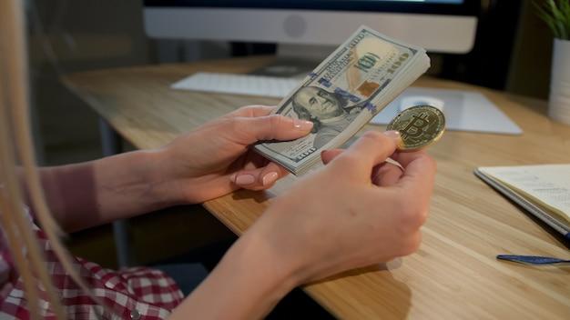 Mujer sosteniendo bitcoin y fajo de billetes