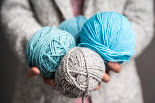 Mujer sosteniendo bolas de hilo de lana de colores