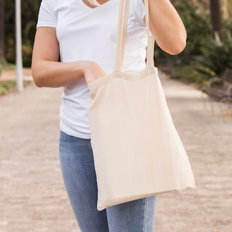 Mujer sosteniendo una bolsa blanca de tiro medio