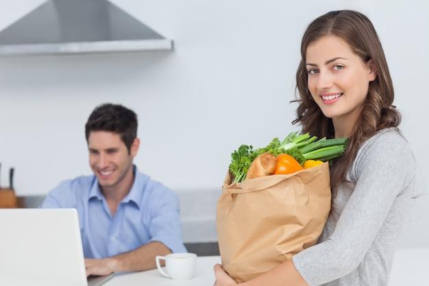 Mujer sosteniendo bolsa de comestibles