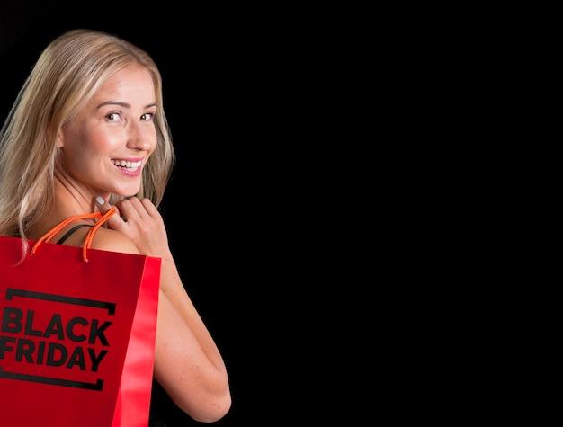 Mujer sosteniendo una bolsa de compras con espacio de copia