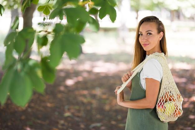 Mujer sosteniendo una bolsa ecológica con espacio de copia