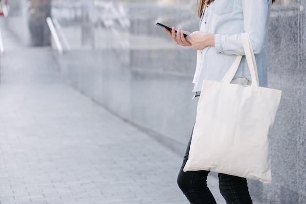 Mujer sosteniendo bolsa ecológica textil blanca contra el fondo urbano de la ciudad. . concepto de protección de la ecología o el medio ambiente. bolsa ecológica blanca para maqueta.