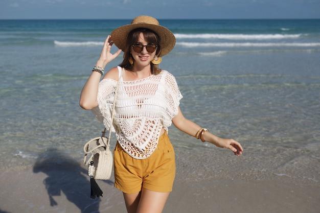 Mujer sosteniendo una bolsa de paja y caminando por la playa