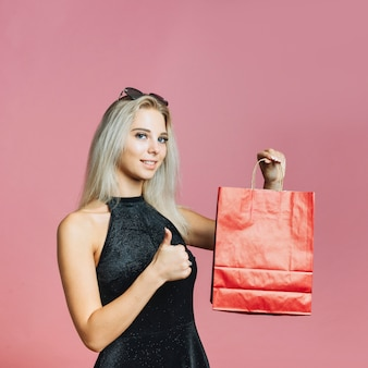 Mujer sosteniendo la bolsa de papel y mostrando el pulgar hacia arriba