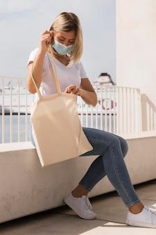 Mujer sosteniendo una bolsa reciclable vista lateral