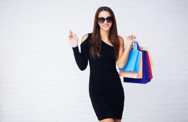 Mujer sosteniendo bolsas de colores en la pared de luz