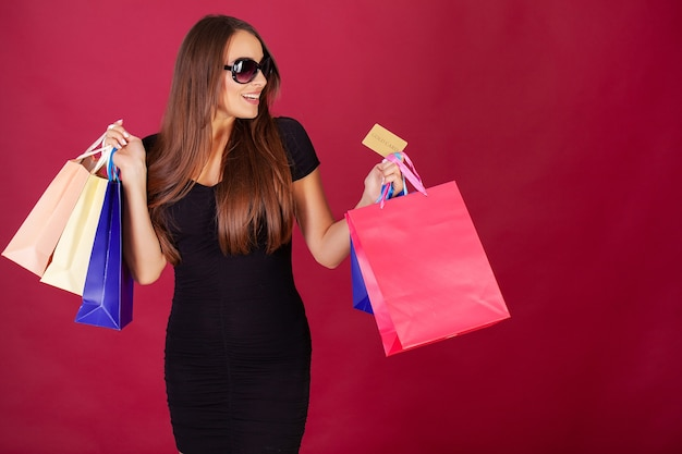 Mujer sosteniendo bolsas de colores y tarjeta de crédito en la pared roja