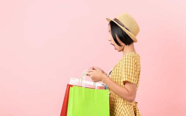 Mujer sosteniendo bolsas de compras multicolores y gritando emocionado sobre fondo rosa.