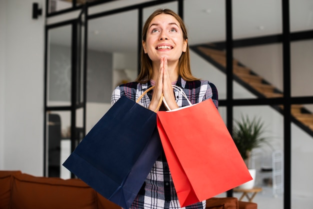Mujer sosteniendo bolsas de papel y rezando
