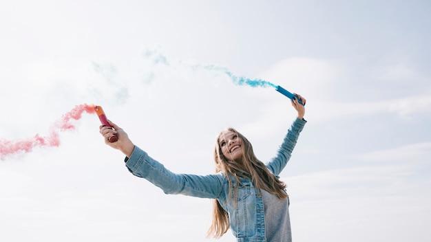 Mujer sosteniendo bombas de humo de colores