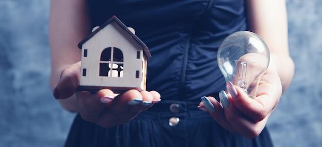 Mujer sosteniendo una bombilla y una casa en sus manos. luz en la casa