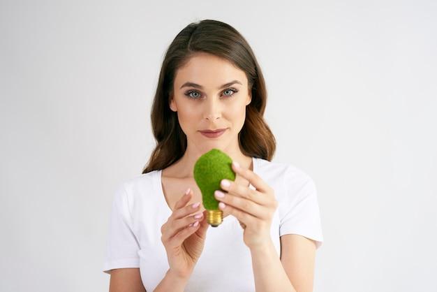 Mujer sosteniendo una bombilla de bajo consumo