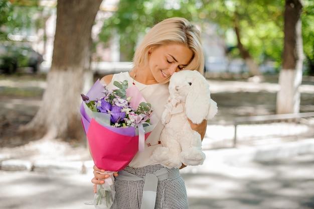 Mujer sosteniendo una bonita composición de flores y juguetes