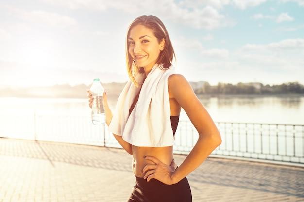 Mujer sosteniendo una botella de agua y una toalla