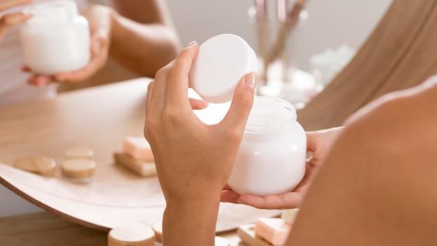 Mujer sosteniendo una botella de crema corporal
