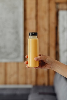Mujer sosteniendo una botella de jugo de naranja