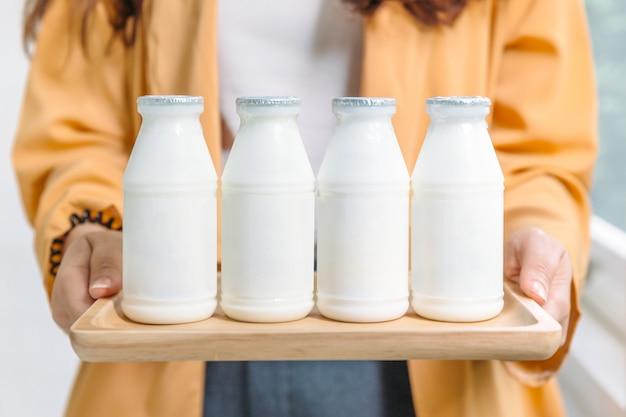 Mujer sosteniendo botellas de leche de yogur pasteurizada