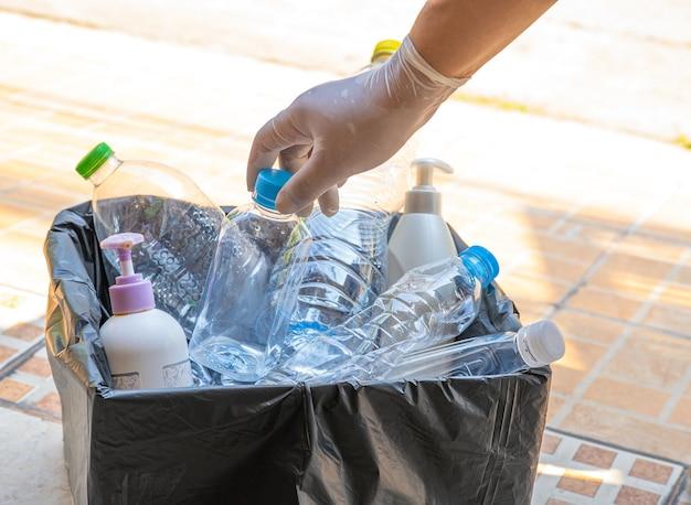 Mujer sosteniendo botellas de plástico basura en caja para reutilizar reciclar.