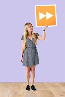 Mujer sosteniendo un botón de avance rápido en un estudio