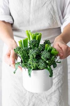 Mujer sosteniendo brócoli orgánico fresco