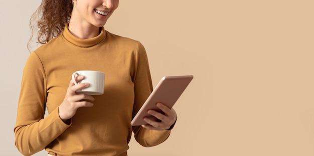 Mujer sosteniendo café de la mañana y usando tableta digital