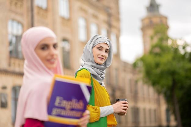 Mujer sosteniendo café. mujer musulmana con café de pie cerca de un amigo mientras camina a clases