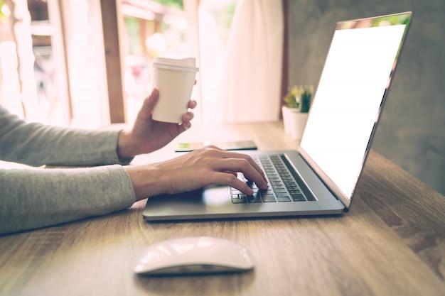 Mujer sosteniendo café y usando la computadora portátil en la mesa de madera en la oficina