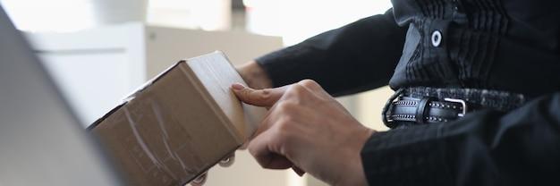 Mujer sosteniendo una caja de cartón delante del concepto de compras en línea de primer plano portátil