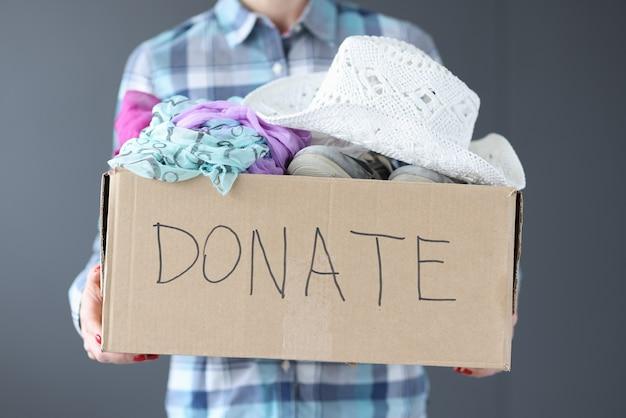 Mujer sosteniendo una caja de cartón con donaciones en su mano closeup