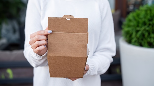Mujer sosteniendo una caja de comida de papel reciclable. idea de reciclaje