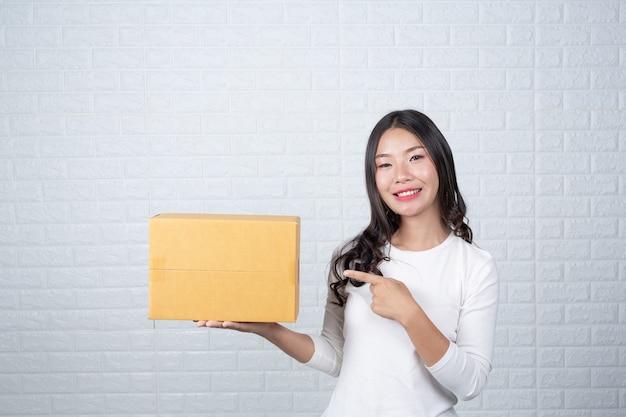 Mujer sosteniendo una caja de correos marrón hizo gestos con lenguaje de señas.