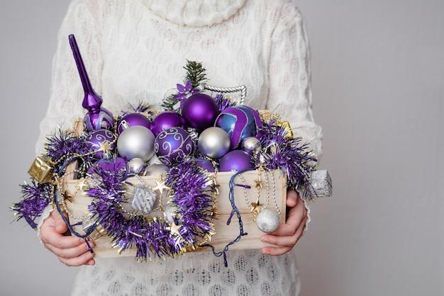 Mujer sosteniendo una caja llena de adornos navideños de color púrpura