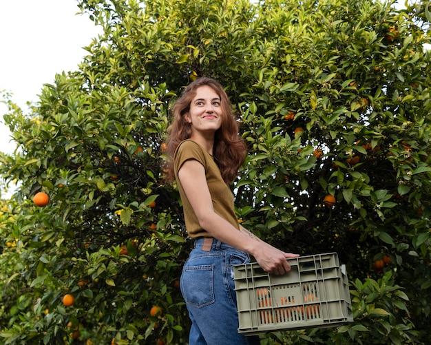 Mujer sosteniendo una caja llena de naranjas en sus manos