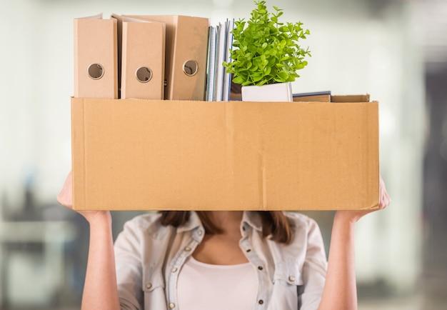 Una mujer sosteniendo una caja en una oficina.