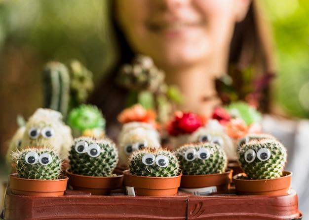 Mujer sosteniendo caja con pequeños cactus con ojos