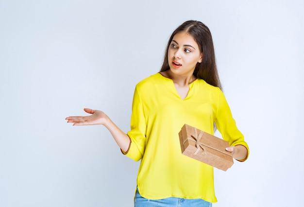 Mujer sosteniendo una caja de regalo de cartón y apuntando a alguien a un lado.
