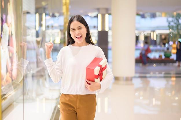 Mujer sosteniendo una caja de regalo en el centro comercial