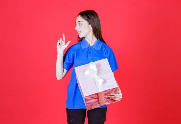 Mujer sosteniendo una caja de regalo rosa atada con una cinta blanca y parece confundida o teniendo una buena idea.