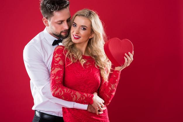 Mujer sosteniendo caja roja y sonriendo amplia