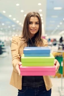 Mujer sosteniendo cajas de compras