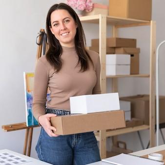 Mujer sosteniendo cajas de tiro medio