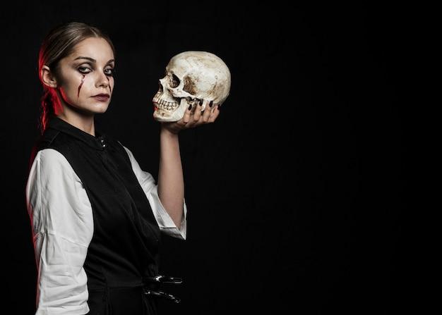 Mujer sosteniendo calavera con espacio de copia