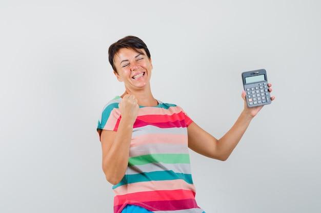 Mujer sosteniendo calculadora en camiseta a rayas y mirando dichoso