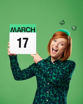 Mujer sosteniendo calendario con una fecha para el día de san patricio