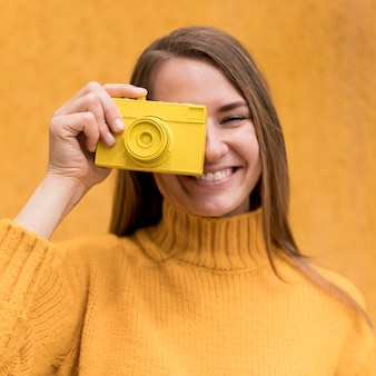 Mujer sosteniendo una cámara amarilla