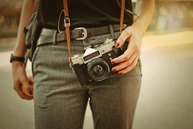 Mujer sosteniendo una cámara retro en la calle